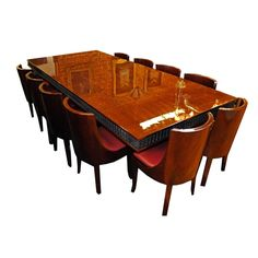 Elegant Art Deco dining set in beautiful French polish finish. The twelve chairs are identical and upholstered in beautiful, supple wine colored leather.
