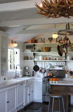 single pot rack over stove, schoolhouse lights, white countertops