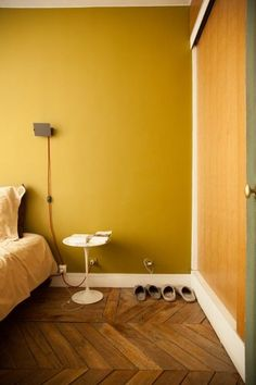 Mustard wall in the bedroom. The Paris apartment of Sabrina Ficarra & Cyril Laborde