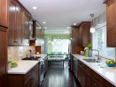This galley kitchen may be on the small side, but there's no shortage of storage space with rich wood cabinets hanging over a textured backsplash and crisp white countertops. A picture window makes doing dishes almost enjoyable while green and blue accessories carry over the color scheme from the dining room.