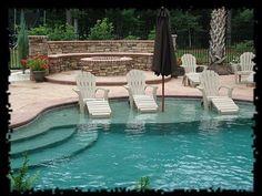 In pool Adirondack chairs with an in-pool  sun umbrella.