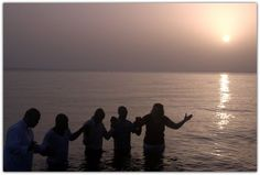 Prayer during the baptism service in the ocean in front of the MOHI missionary compound: