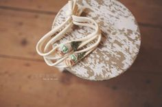 A headband with silk petals, a yarn nest, preserved greenery and a mint freshwater pearlnewborn size