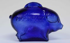 Cobalt Blue Collectible Still Glass Piggy Bank. Molded bank with raised arch slot. Each side of bank is embossed with PIGGY BANK. Bottom