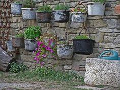Al muretto sono appesi dei vecchi paioli dove vengono coltivate le erbe aromatiche assieme a fiori ornamentali