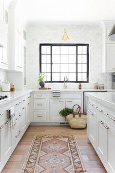 Kitchen with black metal frame window, white oak floors, modern white cabinets with brass pulls and vintage rug.