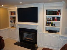 Built-Ins with base cabinet storage, roll out dvd trays, fluted pilasters with recessed panels, boxed mantle shelf with crown moldings