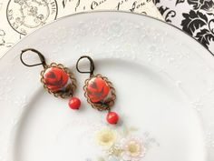 These earrings are made of vintage red rose cameos from Western Germany and set in an antiqued bronze lacey setting. Ive also attached a little red bead under the cameo. The matching lever backs are hypoallergenic. They dangle about 1.75 from the top of the wire. One of a kind!  Comes from a smoke-free and pet-free home.  My vintage pieces are made with OLD materials. Due to their age, vintage pieces may have patina and imperfections, including age spots, scratches, discoloration, and…