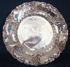 Bandeja de metal espessurado a prata com detalhes de flores no centro e nas bordas. 30cm diâmetro.