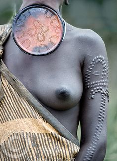 Mursi tribeswoman with large clay lip plate and decorative scarification on her arm. Omo Delta, Ethiopia, Africa.
