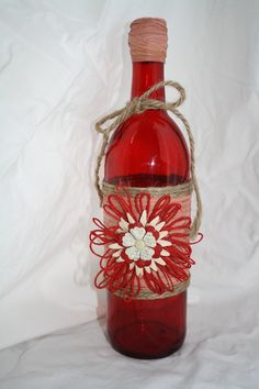 Red glass bottle wrapped in burlap, and twine.  handmade flower accent.