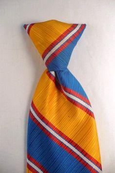 """Authentic 70's vintage clip on tie in bold colored stripes.Length: 18""""Width: 4 1/4""""Authentic Vintage Era: 1970'sLabel/Maker: Sears The Men's Store  SnapperPattern/Design: stripedFabric: Untagged, feels like silk but is likely a high spun, quality polyester.Colors: Red, White, Blue, Yellow Vintage Condition: Excellent"""