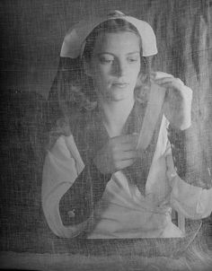 """Nurse. Caption from the July 1, 1940, issue of LIFE. """"Gauze is a basic raw material of every Red Cross unit. Here a volunteer worker prepares a dressing. Making bandages — not knitting — are the main duties of Red Cross volunteers."""""""