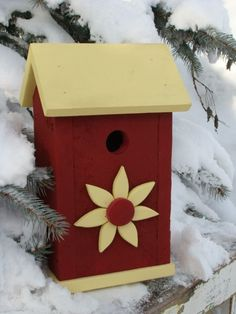 Red and yellow birdhouse with wood flower