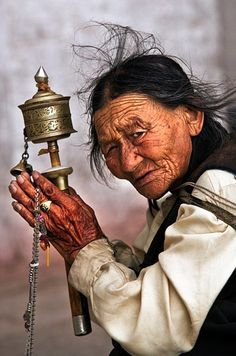 Elderly Tibetan woman with a prayer wheel.