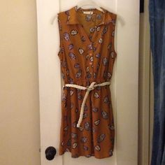 """Mustard/brown dress with leaf detail! EUC This Anthropologie dress (tag says """"Mine"""") is to die for. The white and blue leaf detail make this the perfect addition to your wardrobe for spring. Collar, four button Henley style top, belt loops, and pockets make this dress a breeze to accessorize! Does not come with belt pictured. Runs true to size, in used but great condition.                                             LOWERED FROM $50! Anthropologie Dresses"""