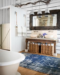 The barn door theme continues in an unexpected spot: a shower stall! Just outside, a towel bar hangs from two ropes.   - CountryLiving.com