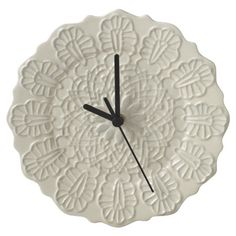 Add a pop of classic style to your home office or kitchen with this charming ceramic wall clock, showcasing a scalloped edge and lace-inspired texture.