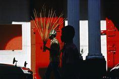 """""""A medida que vagaba por los pórticos del céntrico Port au Prince en 1979, recuerdo ver a este hombre con un ramo de juncos –increíblemente silueteado contra la vibrante pared roja- y justo un segundo hombre, en la sombra apareció de repente. Hice la foto y poco a poco empecé a darme cuenta de que era hora de dejar atrás el blanco y negro."""" Alex Webb  7 fotos que lo cambiaron todo para Magnum"""