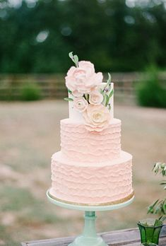 A three-tiered pink wedding cake with soft ruffled details and sugar flowers created by @sugarbeesweets | Brides.com