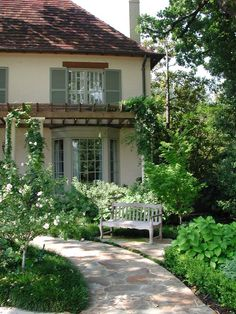 Brown roof, cream stucco, green shutters, bay window, curved walkway, and a charming bench. Heavenly.