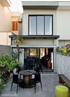 o lazer fica nos fundos. Para garantir privacidade, os muros aumentaram 60 cm com a adição de elementos vazados de concreto e blocos-jardim, nos quais há espaço para cultivar plantas. O beiral metálico (80 cm) protege a entrada da cozinha.