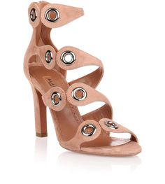 Tan suede sandal with gunmetal eyelet detail from Alaia. The sandal has a 90mm heel, a logo detailed zip at the back and a asymmetrical straps.True to sizeLeather soleMade in ItalyDesigner Colour: Chair