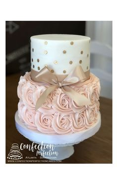 This 2 tier buttercream iced cake has gorgeous pink rosettes on the bottom tier and a smooth white finish with gold dots on the top.  A gold bow is tied at the base of the top tier, as shown.  Color changes can be accommodated.  Please note any writing you would like in our Order Notes section at checkout! ** NOTE: Only our basic flavors are included in our online pricing. If you would like to order premium flavors or fillings, please state the flavors/fillings in the Order Notes section at…