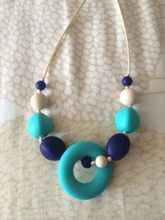 This is a turquoise, cream, and navy BPA free silicone teething necklace for mom (or dad). The necklace is made of small and large round