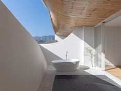 Blocking low-level views also lend the micro yards more privacy, and each contains a bath and seating area covered by a sweeping soffit of wooden planks. Outdoor Bathtub, Small Bathtub, Glass Balcony, Old Farm Houses, Furniture Handles, Dezeen, Ceiling Windows, Sliding Glass Door, White Walls