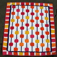 Abacus Baby Quilt - Make bright and cheery baby quilts with this Abacus Baby Quilt pattern. The tiny alternating snowball blocks make this quilt look like an abacus. Choose colors like those in the sample for a baby girl, or select different colors for baby boy quilts.