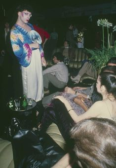 Brightly attired patron uses a fan to cool off in the lounge at New York's Studio 54, March 1979. (AP Photo)
