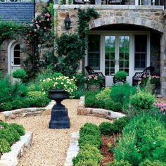 Gravel pea stone path lined with boxwood and a black urn as a focal point.