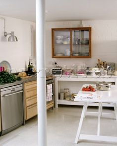 The kitchen area of an open plan room with a stainless steel oven next to a wooden kitchen unit and