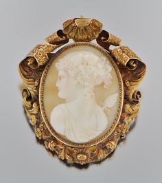 An Oversized Victorian Carved Shell Cameo in Elaborate Frame. Elaborate shell and scroll motif reticulated gold frame features a finely carved cameo of a young lady.