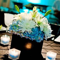 The tables in the ballroom were decorated with three different centerpieces: a tall centerpiece that featured an arrangement of hydrangea mixed with black branches illuminated from the bottom by an LED candle, a low centerpiece of blue and white hydrangea nestled in a black box and non-floral centerpiece featuring a lamp with a black and white damask shade.