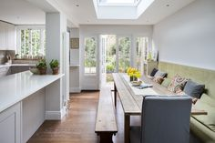 Interior Design by Imperfect Interiors in this Georgian terraced house in London. The perfect mix of old and new- a calm palette of Farrow & Ball colours, antique bench and dining table mixed with composite worktops & a built in bench seating area in this open plan Shaker kitchen diner. Photo by Chris Snook