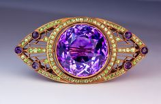 An Impressive Art Deco Amethyst and Demantoid Gold Brooch, Moscow, circa 1930. A 14K gold milgrain openwork brooch in Art Deco style features a large bright purple sparkling Russian amethyst. The well matched sparkling Ural demantoids are of a uniform apple green color.