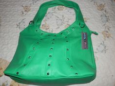 Great green makes this purse stand out! Use this bag to brighten your winter days! Measurements are: 16 inches wide by 10 inches tall. The handle has an 11.5 inch drop. Zip closure with 1 zippered pocket and 2 slip pockets inside. Does have 1 zippered pocket on the back. Faux leather with gold tone studs on the front only. Will hold all those important things us girls have to have!