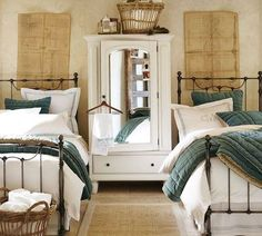 Perfect elements for a guest bedroom: vintage maps, wardrobe, basket full of towels, & layers of linens