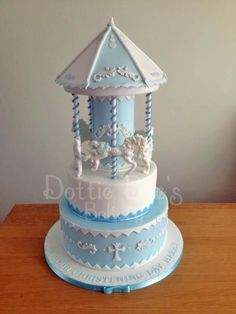 A baby blue christening cake with five horses on a carousel. The bottom tier was chocolate cake and the top vanilla. It had lustred swirls and dots along with the symbolic christening cross