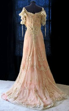 Early 1900s off-the-shoulder lace gown with short train, worn over a pink underdress, the gown is made almost entirely of ecru net embroidered with floral and leaf motifs in the tambour style and enhanced with appliqued lace and cut-work. The neckline and sleeves are trimmed with cotton ruffles, ribbon and lace trims. Pinned by #Blucha from seller's eBay listing