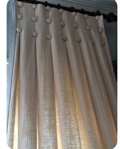 Add box pleats and covered buttons to premade drapes. Widen window look by broadening rod placement.