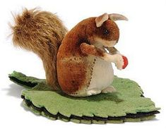 A STEIFF VELVET SQUIRREL PINCUSHION, (3419), brown and white, black bead eyes, felt arms, ears and feet, mohair tail, holding red berry, attached to green and black leaf pin-cushion, circa 1905 --4in. (10.5cm.) long