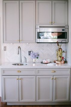 Grey cabinetry with gold accents.