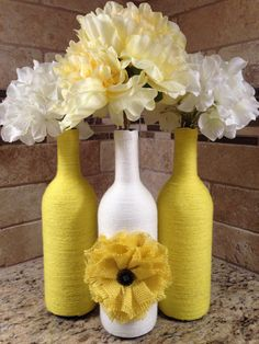 This listing is for a set of three wine bottles which have been hand wrapped in yellow and cream yarn. Center bottle is embellished with a