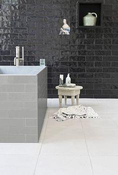 Badkamer tegels: wand met de glanzende reliëf tegel Calpe Concrete. Op de vloer ligt een contrasterende terracotta tegel die mooi mat en groot is: White Touch heeft de uitstraling van witgeverfd beton. Het bad is bekleed met tegel Calpe Seagreen, uit de VT Wonen tegelcollectie #badkamer #tegels