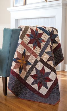 "Blaze of Stars--his traditional quilt features scrappy eight-pointed star blocks and sashing between blocks.This quilt can be sized to full or queen sized and is great practice for set-in seams; check out this free video tutorial.  Size: 70"" × 84"" Blocks: 20 (12"") blocks  Rating: Challenging"