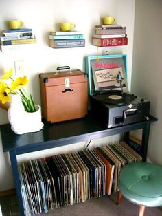 orginization i like the books used as shelving old record player records round small stool teal mustache planter small navy blue desk