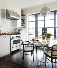In this modern kitchen by designer Mazen El-Abdallah, steel-framed french doors let incredible natural light in, distracting from the space's minimal square-footage. | Photographer: Alex Lukey